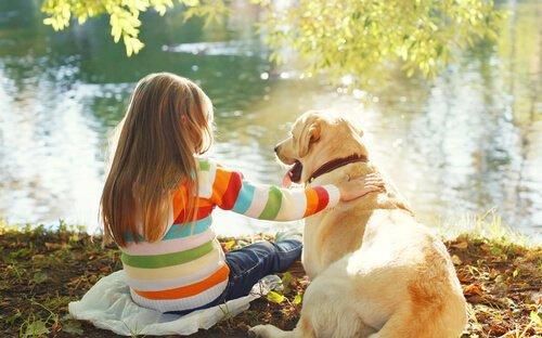 göl kenarında oturan çocuk ve köpeği