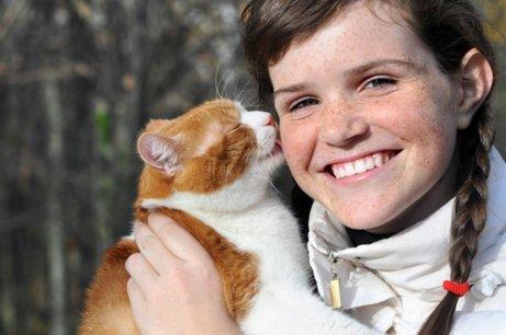 kızın yüzünü yalayan kedi