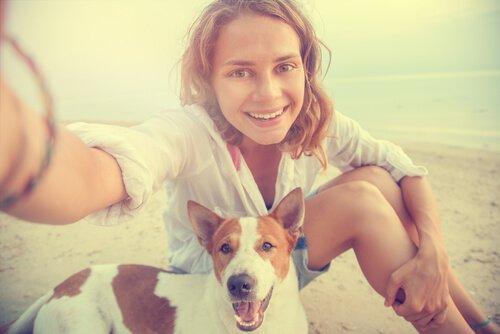 sahilde köpek ile fotoğraf çekinen kadın