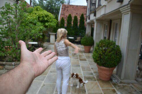 evin bahçesinde duran köpek ve kadın