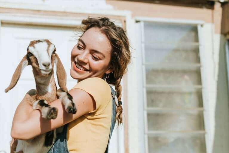 kız keçiyi kucağına alıyor
