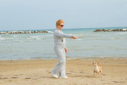 köpeğiyle plajda oynayan kadın