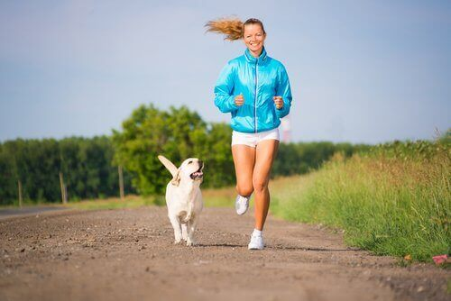Köpeği ile birlikte egzersiz yapan bir kadın.